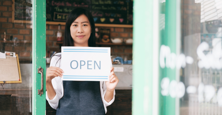 A female business owner holds up an open sign in front of her shop.